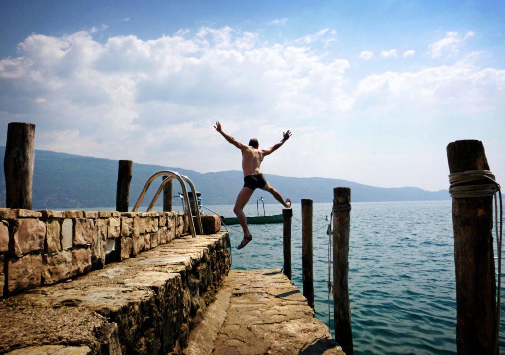 Homme sautant de joie dans un lac